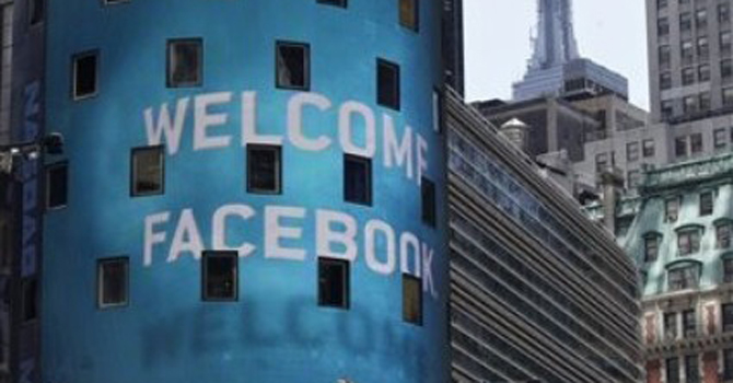 The top of the Empire State Building, top right, is visible behind the animated facade of the Nasdaq MarketSite, welcoming the Facebook IPO, in New York's Times Square.—AP Photo