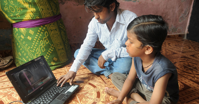 Video journalist and slum dweller Amol Lalzare, 27, (L) shows his seven year-old nephew Anmol one of his news reports on his laptop at his room in the Sathe Nagar slums of Mumbai.—AFP Photo