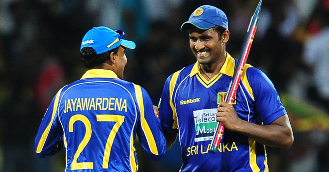 Thisara Perera celebrates with captain Mahela Jayawardene after taking six wickets that brought Sri Lanka victory. ? Photo by AFP
