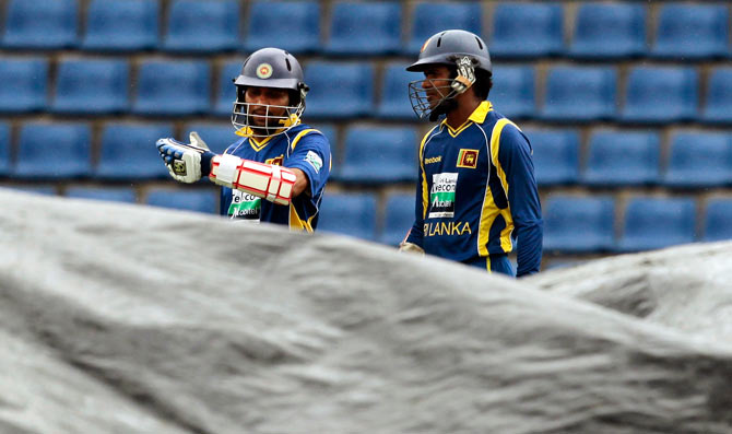 Tilikaratne Dilshan and Upul Tharanga walk off as play is interrupted by rain. ? Photo by AP