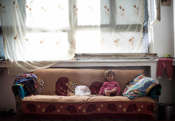 A Roma child sits on a couch in her new home inside a former processing plant turned into a housing project in Baia Mare.