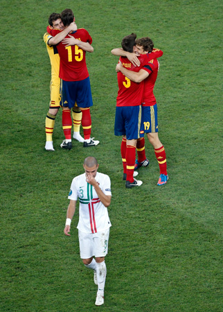Portugal's Pepe leaves the pitch as Spanish players celebrate winning the Euro 2012 semi-finals. ? Photo by AP