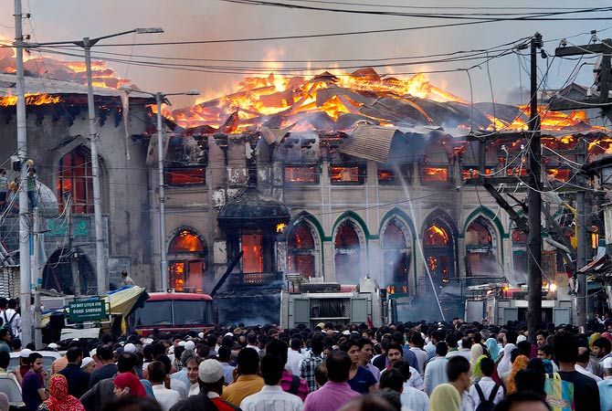 Kashmiri residents watch as firefighters try to extinguish a fire at the nearly 200-years-old Sheikh Abdul Qadir Jeelani Shrine, popularly known as Ghaus-e-Azam,or Dastgeer Sahab, in downtown Srinagar, India, Monday, May 25, 2012. — AP Photo