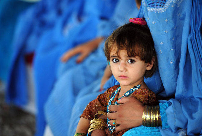 An Afghan girl sits with her mother at The United Nations High Commissioner for Refugees (UNHCR) registration centre on the outskirts of Peshawar. ? Photo by AFP