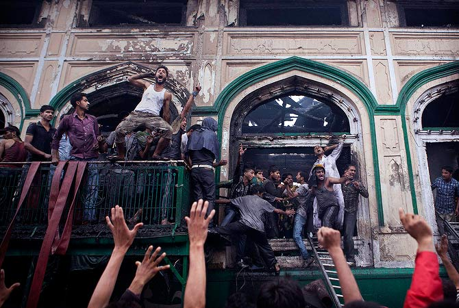 Kashmiri Muslims shout religious slogans after retrieving relics from the nearly 200-years-old Sheikh Abdul Qadir Jeelani Shrine, popularly known as Ghaus-e-Azam, or Dastgeer Sahab, after it caught a fire in downtown Srinagar, India, Monday, May 25, 2012. — AP Photo