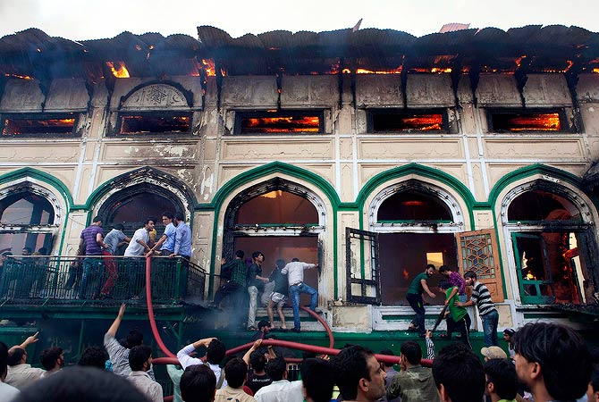 Residents try to put out a fire at the nearly 200-years-old Sheikh Abdul Qadir Jeelan Shrinei, popularly known as Ghaus-e-Azam, or Dastgeer Sahab, in downtown Srinagar, India, Monday, May 25, 2012. — AP Photo