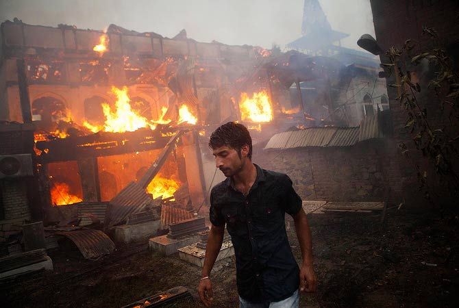 A Muslim boy walks past the nearly 200-year-old Sheikh Abdul Qadir Jeelani Shrine, popularly known worldwide as Ghaus-e-Azam or Dastgeer Sahab, on fire in downtown Srinagar, India, Monday, May 25, 2012. Anti-India clashes between protesters and government forces erupted in the main city in Indian-controlled Kashmir Monday after the highly revered Muslim shrine was destroyed in a fire, police said. The cause of the fire is yet unknown. — AP Photo