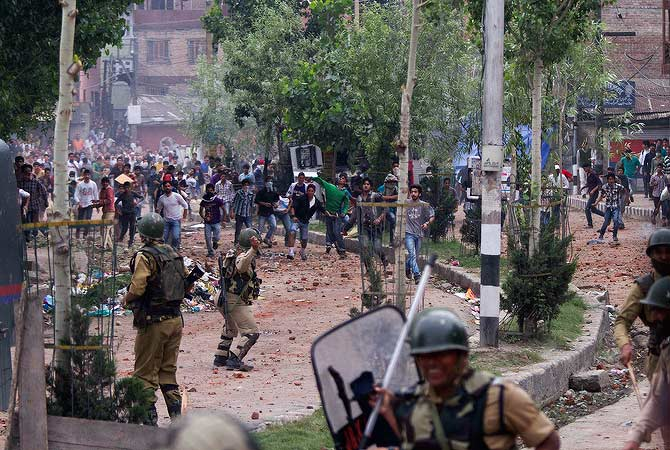 Kashmiri Muslim protesters and Indian paramilitary soldiers throw rocks and bricks at each other during anti-government protests after a fire destroyed a revered Muslim shrine in Srinagar, India, Monday, June 25, 2012. — AP Photo