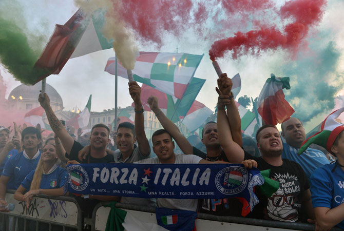 Supporters of the Italian national football team cheer and use flares as they watch the Euro 2012 semifinal football match.