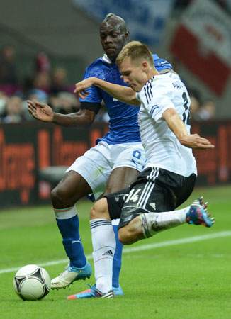 German defender Holger Badstuber (Right) vies with Italian forward Mario Balotelli during the Euro 2012 football championships semi-final match Germany vs Italy.