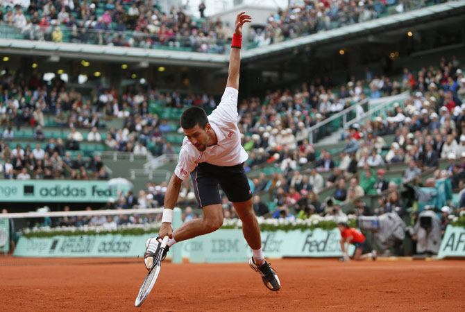 Serbia's Novak Djokovic falls as he plays with France's Jo-Wilfried Tsonga during their Men's Singles Quaterfinals tennis match. ? Photo by AFP