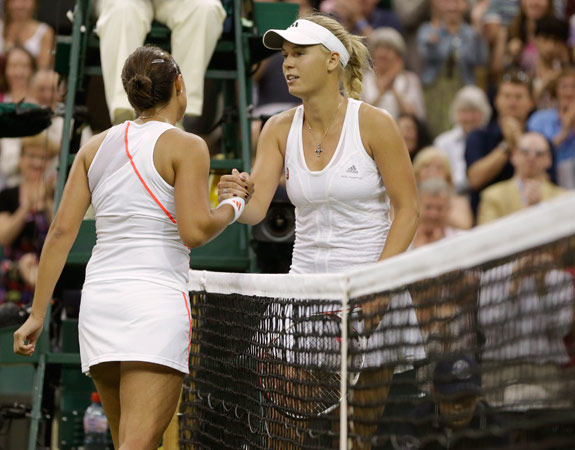 Caroline Wozniacki of Denmark, right, congratulates Tamira Paszek of Austria after she lost their first round women's singles match. – Photo by AP