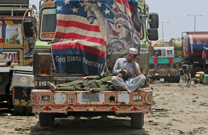 A man speaks on his mobile phone while another rests his head on his lap on the bumper of an oil tanker used to transport NATO fuel supplies to neighbouring Afghanistan in Karachi, June 10, 2012. – Photo by AP