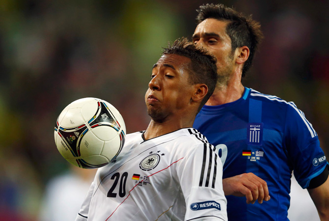 Germany's Jerome Boateng (Left) is challenged by Greece's Sokratis Papastathopoulos during their Euro2012 quarter-final soccer match.