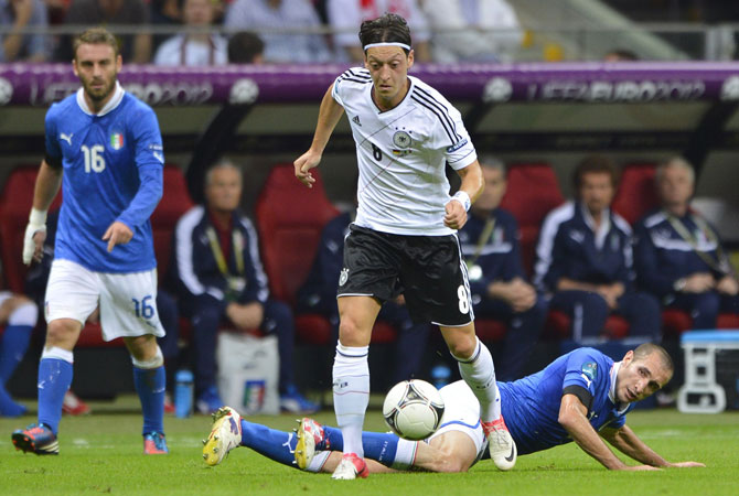 German midfielder Mesut Ozil vies with Italian defender Giorgio Chiellini during the Euro 2012 semi-finals.