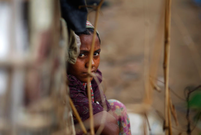 A Rohingya Muslim woman sits at the entrance of her home at an unauthorized camp that houses Rohingya Muslim refugees who fled Myanmar during an ethnic strife in 1992, at Kutupalong, Bangladesh. ? Photo by AP