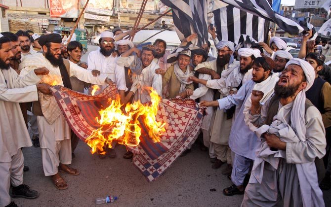 Supporters of Pakistan Defense Council burn a representation of a US flag at a rally to condemn the reopening of the NATO supply line in Quetta, June 1, 2012. – Photo by AP