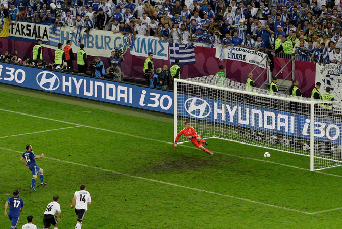 Greece's Dimitris Salpingidis scores a penalty kick against Germany's goalkeeper Manuel Neuer (Right) during their Euro 2012 quarter-final soccer match.