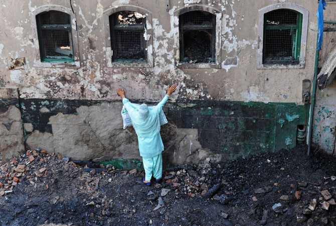 A Kashmiri Muslim woman grieves as unseen fire services personnel and volunteers clear debris from the charred remains of the shrine.