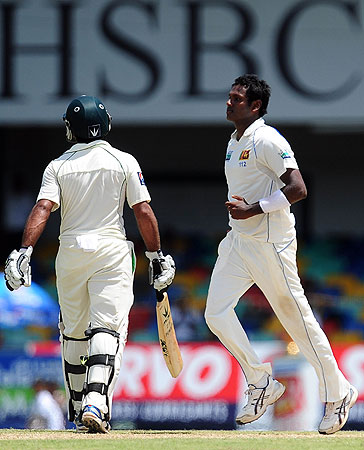 Umar was eventually dismissed by Angelo Mathews (R), edging a half-tracker to the keeper. -Photo by AFP