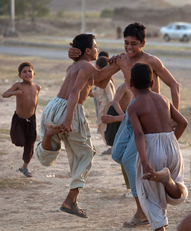 "Refugee children, who fled their villages due to a crackdown by authorities against militants in Pakistani tribal areas, play a traditional game called ""Kabadi"", in Islamabad, June 8, 2012. – Photo by AP"