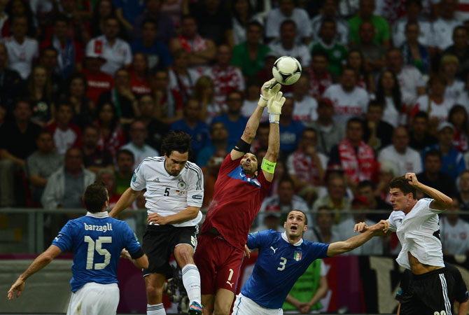 Italian goalkeeper Gianluigi Buffon jumps for the ball next to German defender Mats Hummels.