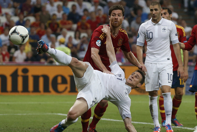 France's Laurent Koscielny is challenged by Spain's Xabi Alonso. ? Photo by Reuters