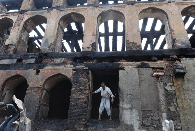 A Kashmiri Muslim volunteer helps clear debris inside the charred remains of the 200-year old shrine of Sheikh Abdul Qadir Jeelani, also known as Dastigheer Sahib, in downtown Srinagar.
