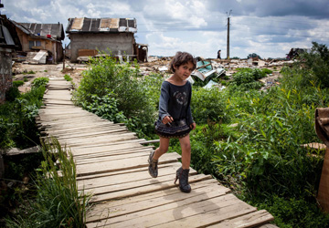 A Roma girl, wearing women's boots, crosses a bridge in Craica. Several rights groups accused the local authorities of ?violating legislation and trampling the dignity of Roma inhabitants.