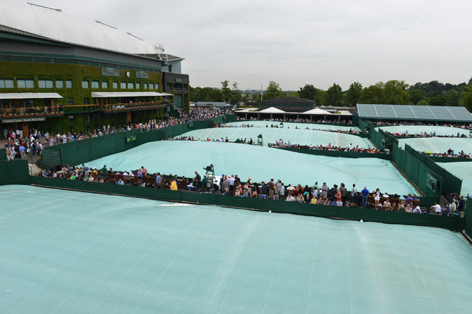 Covers on the outside courts during a rain shower on day three of the 2012 Wimbledon Championships tennis tournament. – Photo by AFP