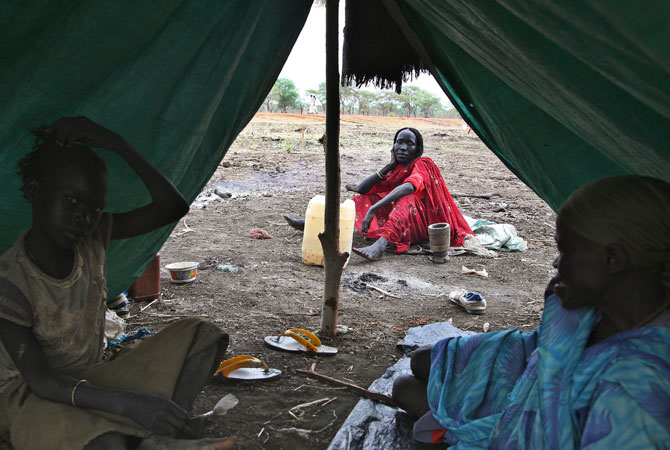 Refugees sitting under a shelter at a transit site where tens of thousands of people have gathered in South Sudan's Upper Nile state near the border with Sudan.- Photo by AFP