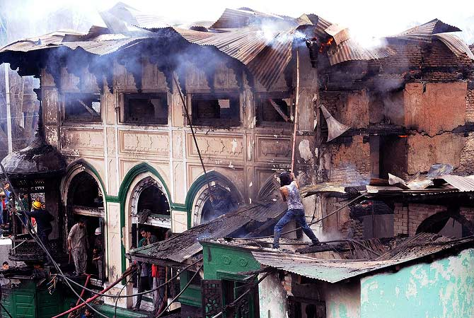Kashmiri residents help firefighters as a fire rages at the sufi shrine of Sheikh Abdul Qadir Geelani known as Dastageer Sahib in downtown Srinagar on June 25, 2012.  A massive fire has broken out in the 200 year old heritage Sufi shrine however, officials said the anciet relics of the saint kept inside a fire-proof safe at the shrine have been saved and retrieved.  — AFP Photo