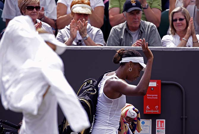 Venus Williams of the United States, right, gestures as she leaves after she was defeated by Elena Vesnina of Russia, foreground left, following a first round women's singles match at the All England Lawn Tennis Championships at Wimbledon, England, Monday, June 25, 2012. ? AP Photo