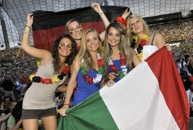 Fans of the Italian and German teams pose with national flags as they watch the Euro 2012 semi-finals.