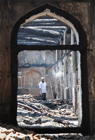 A Kashmiri Muslim volunteer looks on as he helps clear debris inside the charred remains of the shrine.