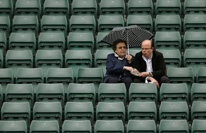 Spectators sit under an umbrella as rain delays play between Samantha Stosur of Australia and Arantxa Rus of Netherlands. – AP Photo