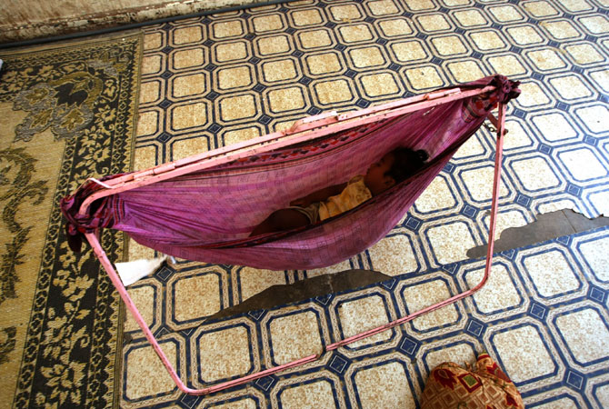 A refugee child sleeps in a hammock in a public school in the port city of Aden, now being used as the living quarters for internally displaced families. ? Photo by AFP