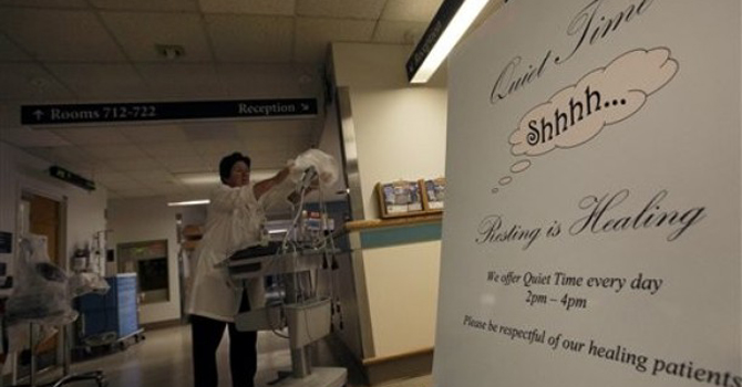 "A sign is posted for ""quiet time"" while Nursing Director Theresa Capodilupo works under dimmed lighting in the hall of the Surgical Trauma Unit at the Massachusetts General Hospital in Boston. – AP"