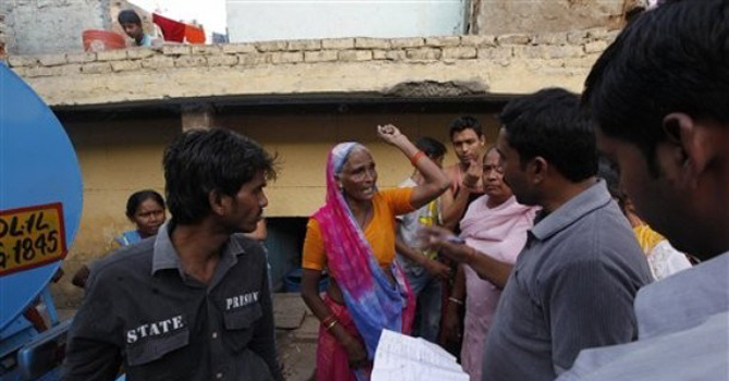 An Indian woman complains of the shortage of water to an official in New Delhi, India. – AP