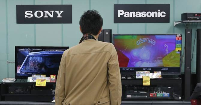 A man looks at Sony and Panasonic TV sets at an electronics shop in Tokyo. – Reuters