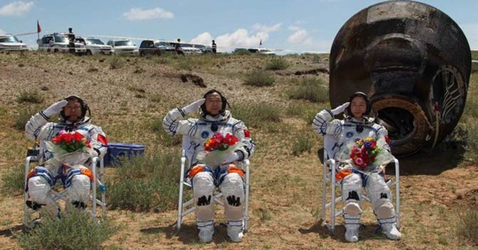 Chinese astronauts Jing Haipeng (C), Liu Wang (L) and Liu Yang, China's first female astronaut, salute in front of the re-entry capsule of China's Shenzhou 9 spacecraft. – Reuters