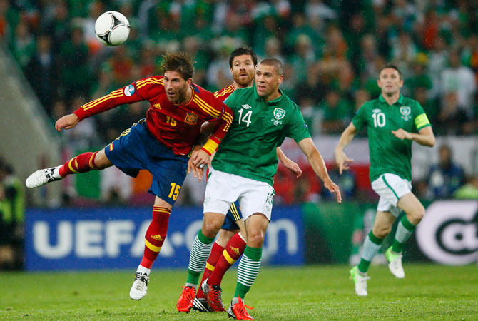 Spain's Xabi Alonso and Sergio Ramos jump for the ball with Ireland's Jon Walters during their Group C Euro 2012 football match. ? Photo by Reuters