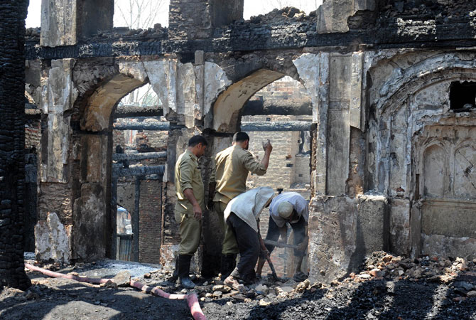 Fire services personnel and volunteers clear debris inside the charred remains of the 200-year old shrine.
