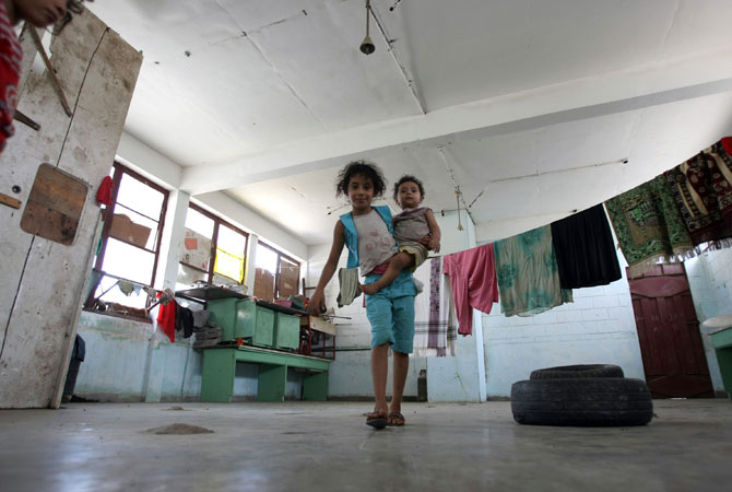 A Yemeni refugee girl carries her sibling in the grounds of a public school in the port city of Aden, now being used as the living quarters for internally displaced families who had to flee their homes when Al-Qaeda militants swept into southern Abyan province. ? Photo byAFP