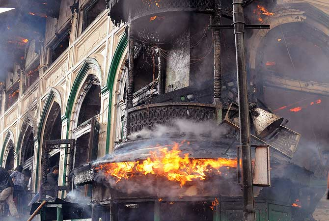 Residents help firefighters as a fire rages at the sufi shrine of Sheikh Abdul Qadir Geelani known as Dastageer Sahib in downtown Srinagar on June 25, 2012.  A massive fire has broken out in the 200 year old heritage Sufi shrine however, officials said the anciet relics of the saint kept inside a fire-proof safe at the shrine have been saved and retrieved. — AFP Photo