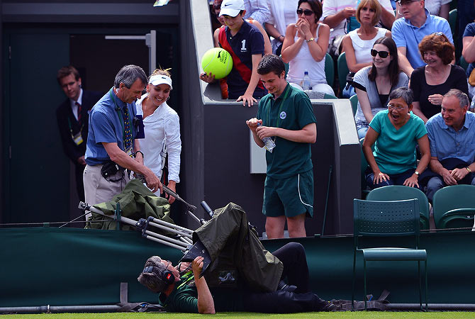 Russia's Elena Vesnina (3rd L) smiles as she watches a BBC TV cameraman take a tumble onto No 2 Court after her match with US player Venus WIlliams on the first day of the 2012 Wimbledon Championships tennis tournament at the All England Tennis Club in Wimbledon, southwest London, on June 25, 2012. ? AFP Photo