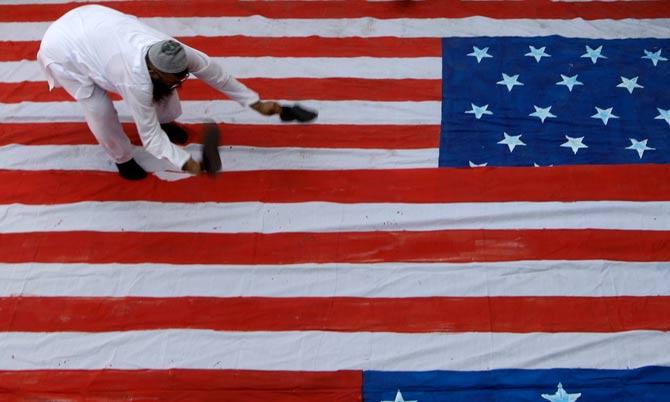 In this Friday, April 6, 2012 file photo, a supporter of group Jamaat-ud-Dawwa stands on a representation of a US flag before setting it on fire during a protest rally in Karachi. – Photo by AP