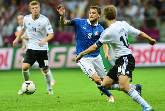 Italian midfielder Claudio Marchisio vies with German defender Philipp Lahm during the semi-final match.
