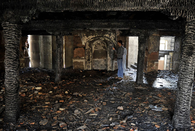 A Kashmiri Muslim looks on inside the charred remains of the 200-year old shrine of Sheikh Abdul Qadir Jeelani.