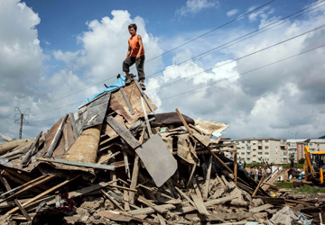 A Roma boy climbs on the top of a house, torn down by local authorities, in Craica.